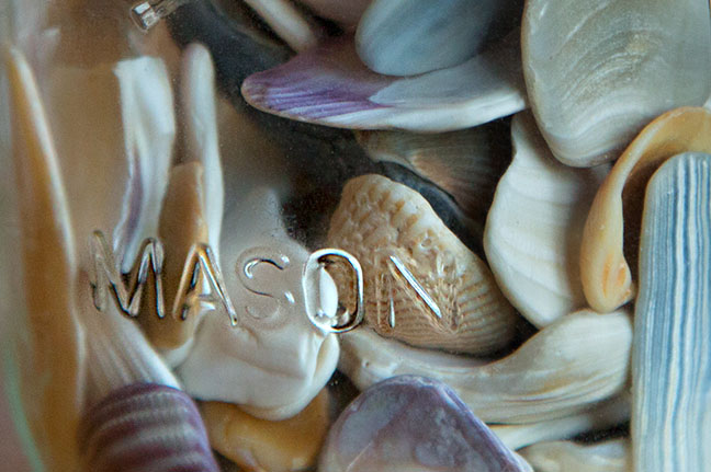 In the living room. Photo of the base of a lamp made up of a mason jar and seashells