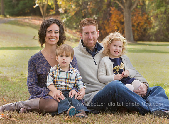 This is a great pose for 2 young children and 2 adults. Having the children in the laps of their parents covers a part of their bodies and they take less space in the photo.